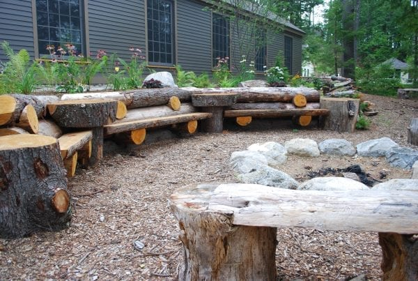 Wood benches around firepit by Belknap Landscape Co